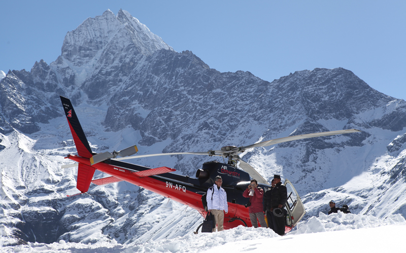 Helicopter resting beside a mountain